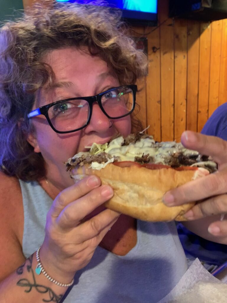 Michelle taking a big bite of a Cheese steak